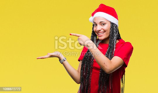 istock Young braided hair african american girl wearing christmas hat over isolated background amazed and smiling to the camera while presenting with hand and pointing with finger. 1056672772
