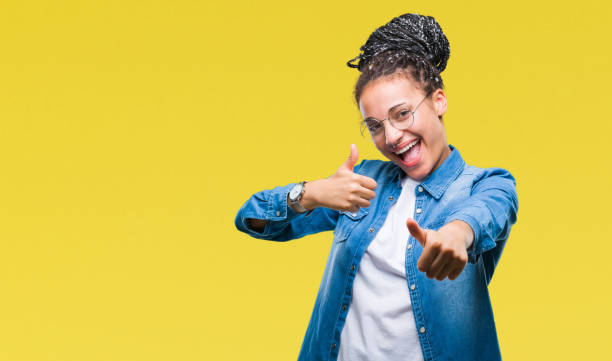 young braided hair african american girl wearing glasses over isolated background approving doing positive gesture with hand, thumbs up smiling and happy for success. looking at the camera, winner gesture. - thumbs up стоковые фото и изображения