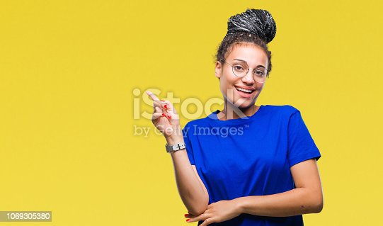 istock Young braided hair african american girl wearing glasses over isolated background with a big smile on face, pointing with hand and finger to the side looking at the camera. 1069305380