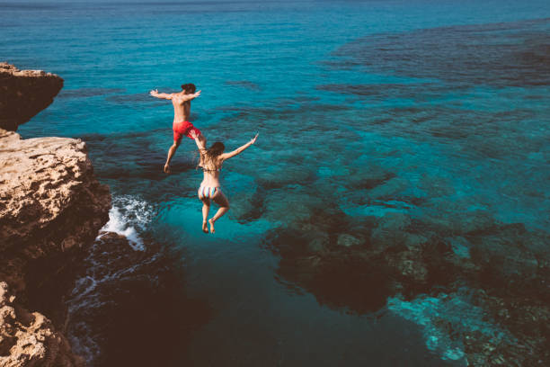 Young brave divers couple jumping off cliff into ocean Young active man and woman diving from high cliff into tropical island blue sea water mid air stock pictures, royalty-free photos & images