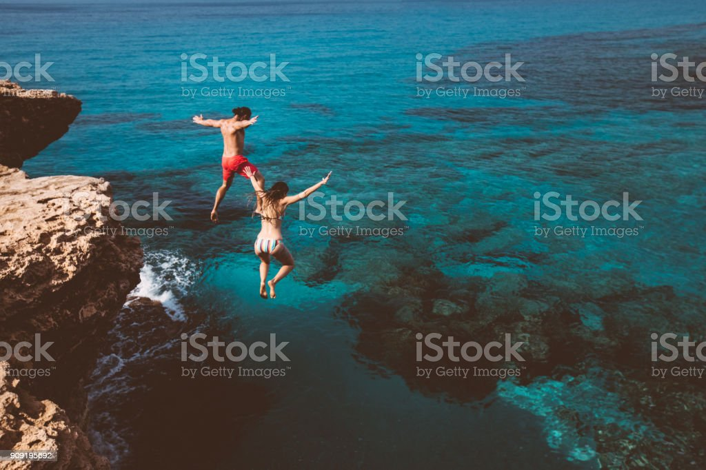 Young brave divers couple jumping off cliff into ocean stock photo