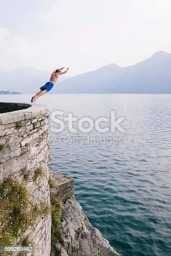 istock Young brave man diving in the water from a cliff. 599269462