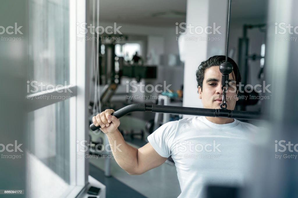 young brazilian athlete pulling weitght at exercise machine stock photo