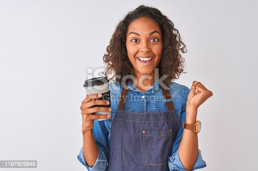 Young brazilian barista woman drinking take away coffee over isolated grey background screaming proud and celebrating victory and success very excited, cheering emotion
