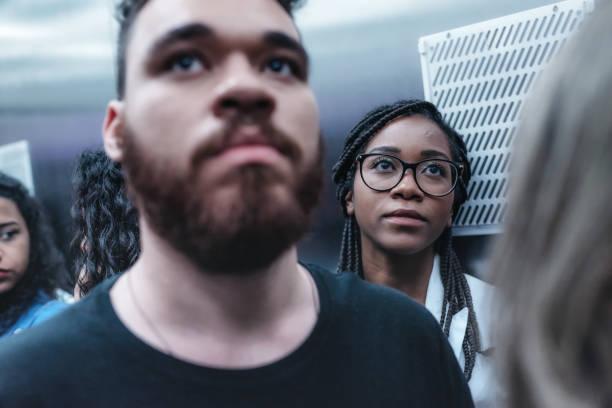 jonge braziliaanse zakenlieden binnenkant lift - claustrofobie stockfoto's en -beelden