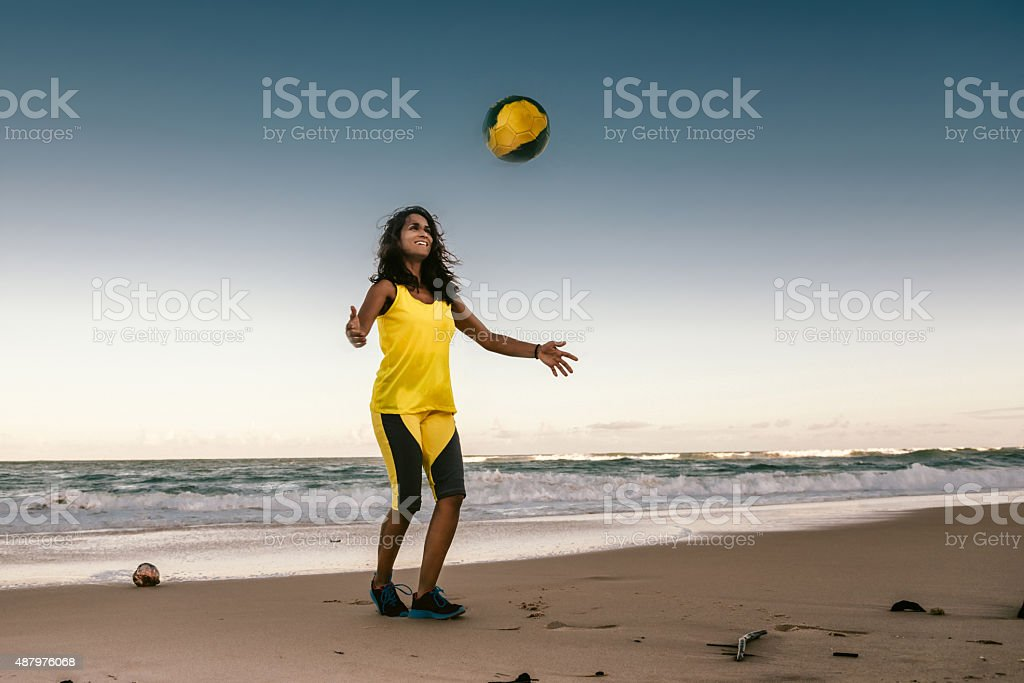 young brazilian girl playing beach soccer at evening stock photo