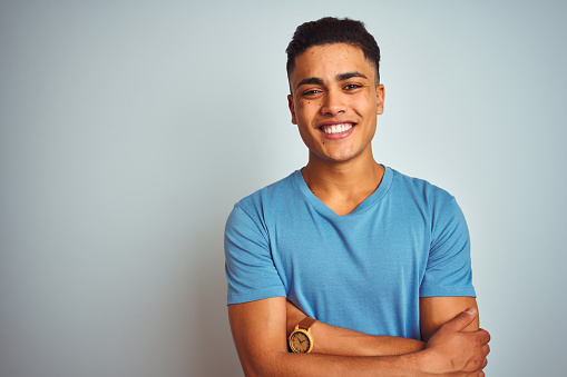 Young brazilian man wearing blue t-shirt standing over isolated white background happy face smiling with crossed arms looking at the camera. Positive person.