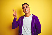 istock Young brazilian man wearing purple sweatshirt standing over isolated yellow background smiling looking to the camera showing fingers doing victory sign. Number two. 1162358204