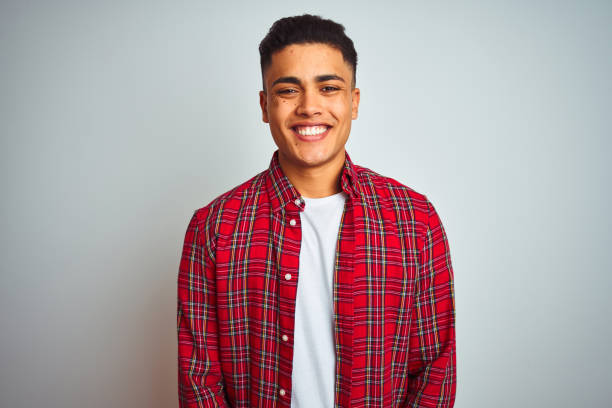 Young brazilian man wearing red shirt standing over isolated white background with a happy and cool smile on face. Lucky person. Young brazilian man wearing red shirt standing over isolated white background with a happy and cool smile on face. Lucky person. red shirt stock pictures, royalty-free photos & images