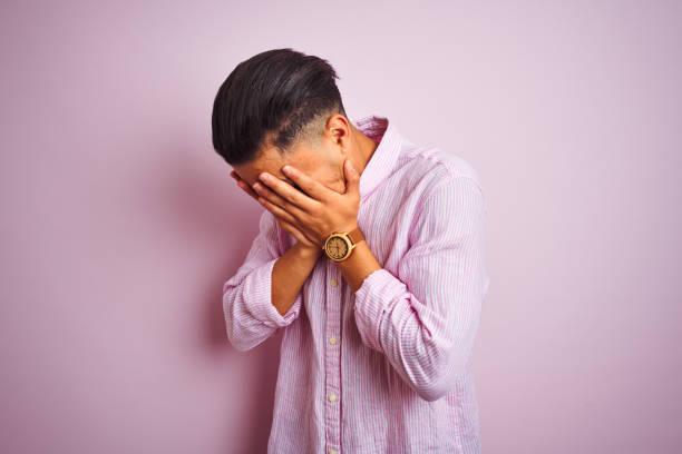 joven brasileño con camisa de pie sobre fondo rosa aislado con expresión triste cubriendo la cara con las manos mientras llora. concepto de depresión. - vergüenza fotografías e imágenes de stock