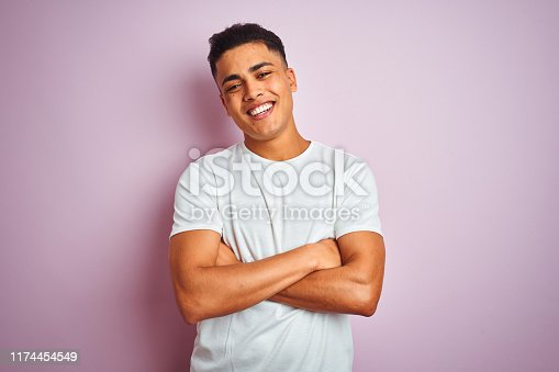 istock Young brazilian man wearing t-shirt standing over isolated pink background happy face smiling with crossed arms looking at the camera. Positive person. 1174454549