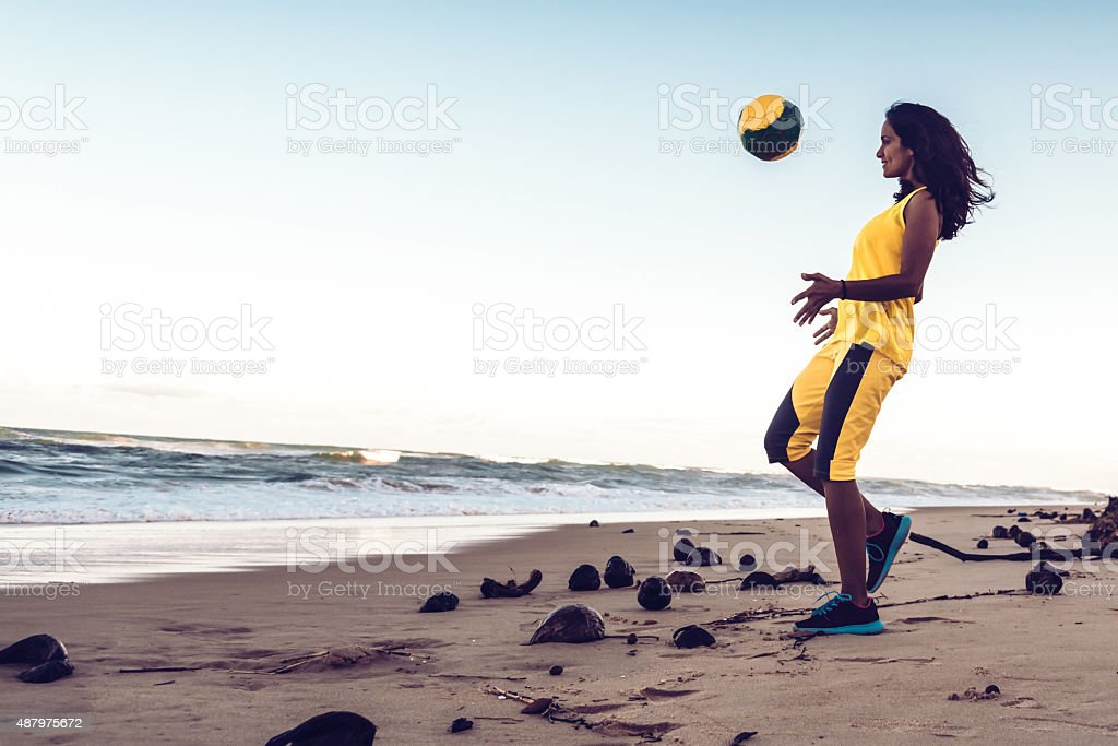 young brazilian woman playing soccer at beach stock photo