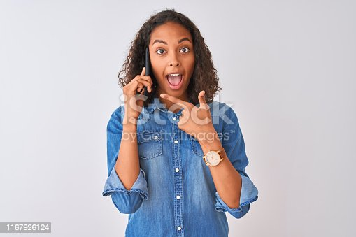 istock Young brazilian woman talking on the smartphone standing over isolated white background very happy pointing with hand and finger 1167926124