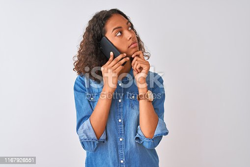 istock Young brazilian woman talking on the smartphone standing over isolated white background serious face thinking about question, very confused idea 1167926551