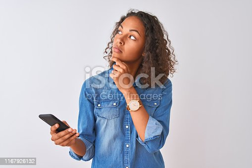 640046924 istock photo Young brazilian woman using smartphone standing over isolated white background serious face thinking about question, very confused idea 1167926132
