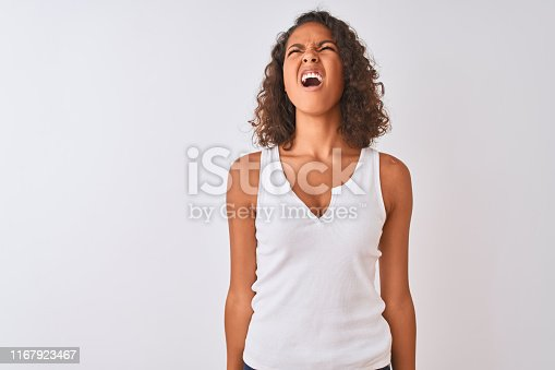 808681534 istock photo Young brazilian woman wearing casual t-shirt standing over isolated white background angry and mad screaming frustrated and furious, shouting with anger. Rage and aggressive concept. 1167923467