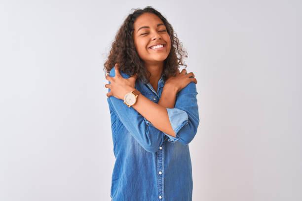 jeune femme brésilienne utilisant la chemise de denim restant au-dessus du fond blanc d'isolement se resplant heureux et positif, souriant confiant. amour de soi et autosoin - femme seule s'enlacer photos et images de collection
