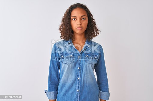 istock Young brazilian woman wearing denim shirt standing over isolated white background Relaxed with serious expression on face. Simple and natural looking at the camera. 1167925805