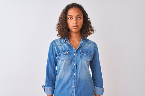 Young brazilian woman wearing denim shirt standing over isolated white background Relaxed with serious expression on face. Simple and natural looking at the camera.