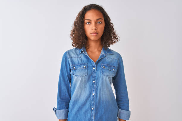 young brazilian woman wearing denim shirt standing over isolated white background relaxed with serious expression on face. simple and natural looking at the camera. - pics for cool girl stock pictures, royalty-free photos & images