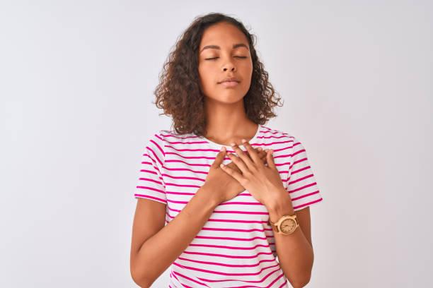 junge brasilianische frau trägt rosa gestreiftes t-shirt, das über einem isolierten weißen hintergrund steht und mit händen auf der brust mit geschlossenen augen und dankbarer geste im gesicht lächelt. gesundheitskonzept. - die wahrheit tut weh stock-fotos und bilder