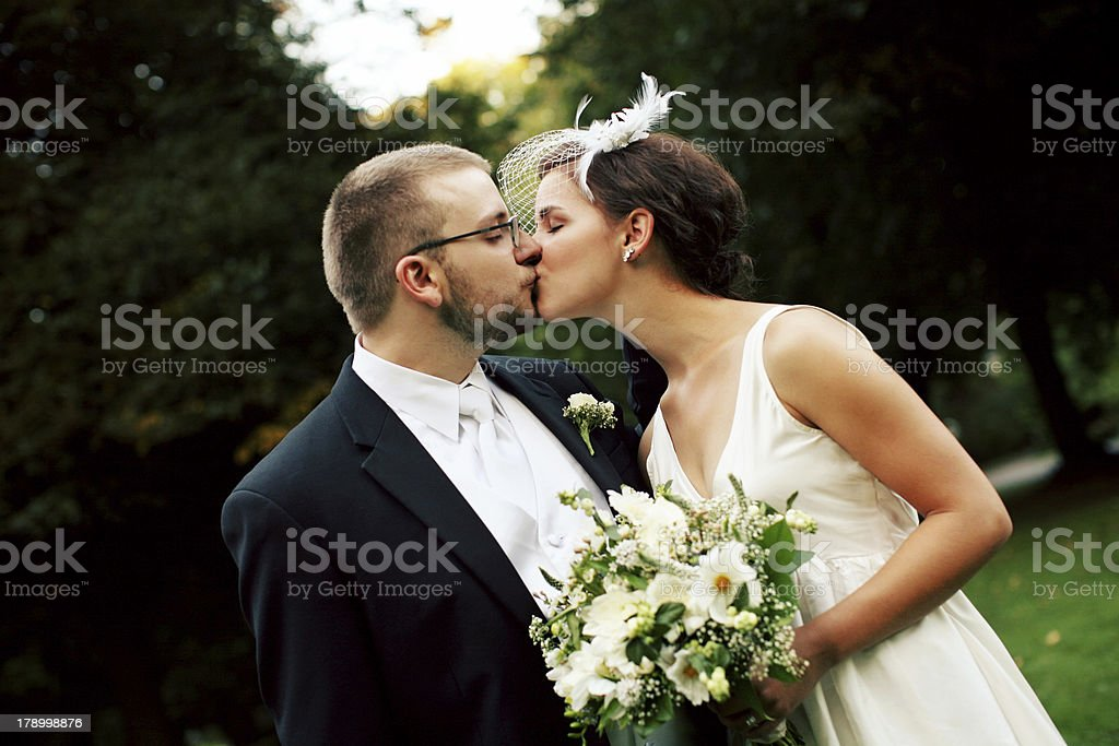 Young Bride and Groom Kissing in a Park royalty-free stock photo