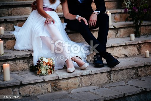 Close-up of newlywed couple's feet sitting on stone stairs and relaxing at wedding reception