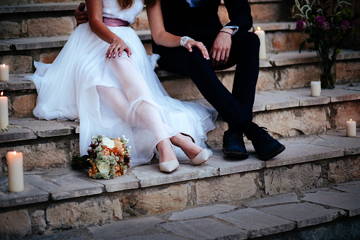 istock Young bride and groom relaxing together on stone steps 929779802