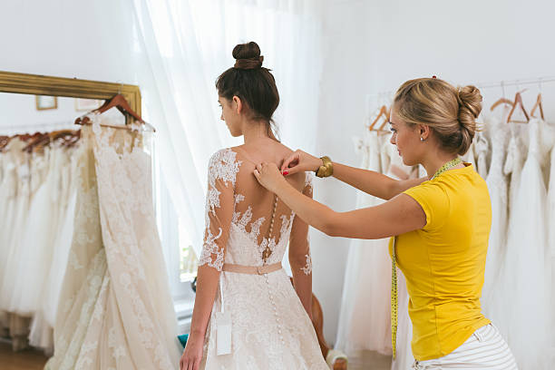 young bride being helped into her wedding dress stock photo
