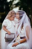Little cute flower girl holding flower basket and hugging with bride at garden wedding ceremony