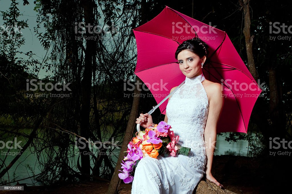 Young Bride Holding Pink Umbrella and Bouquet Outdoors near Lake foto royalty-free