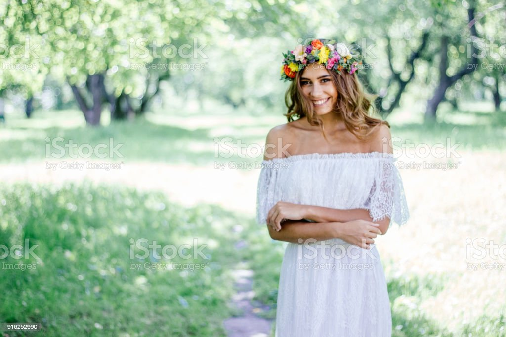 Young bride in a wedding dress staying on a forest. stock photo