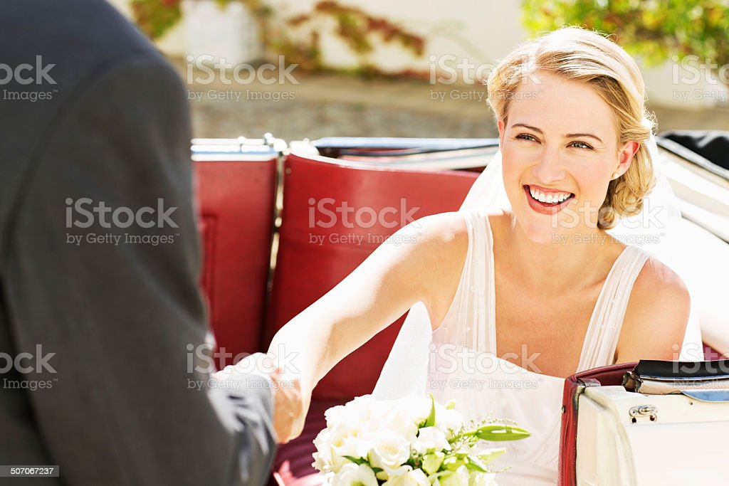 Young Bride In Getting Off From Convertible Car stock photo