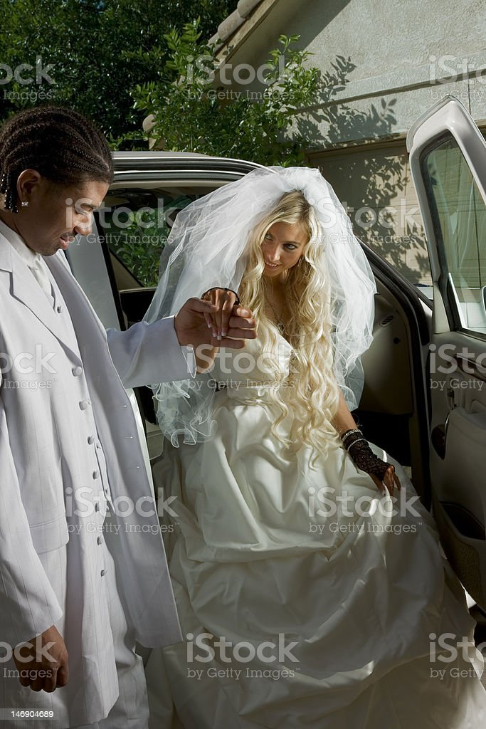 Young bride in wedding dress getting off car royalty-free stock photo
