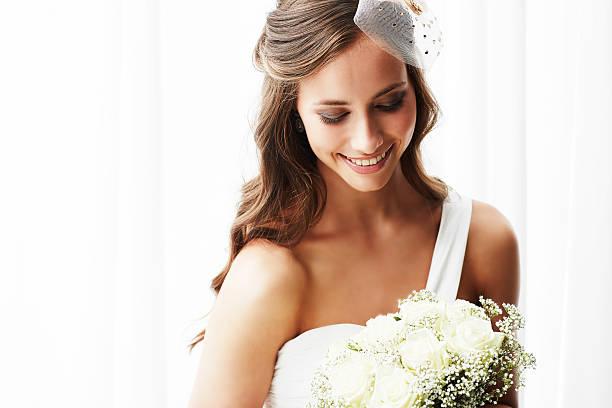 młody panna młoda w sukni ślubnej, trzymając bukiet, ujęcie studyjne - panna młoda zdjęcia i obrazy z banku zdjęć