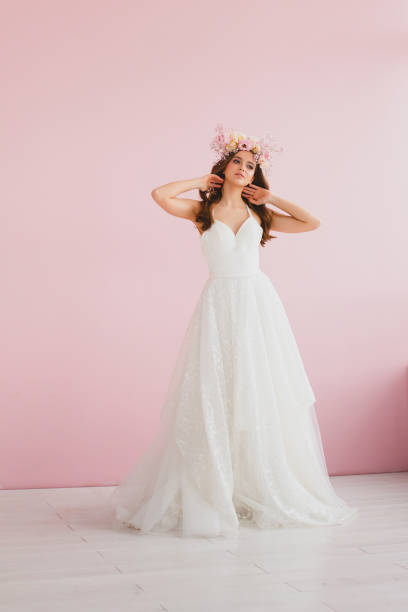 Young bride in white dress with flower wreath on her head posing in the studio stock photo