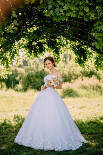 young bride is standing in summer garden stock photo