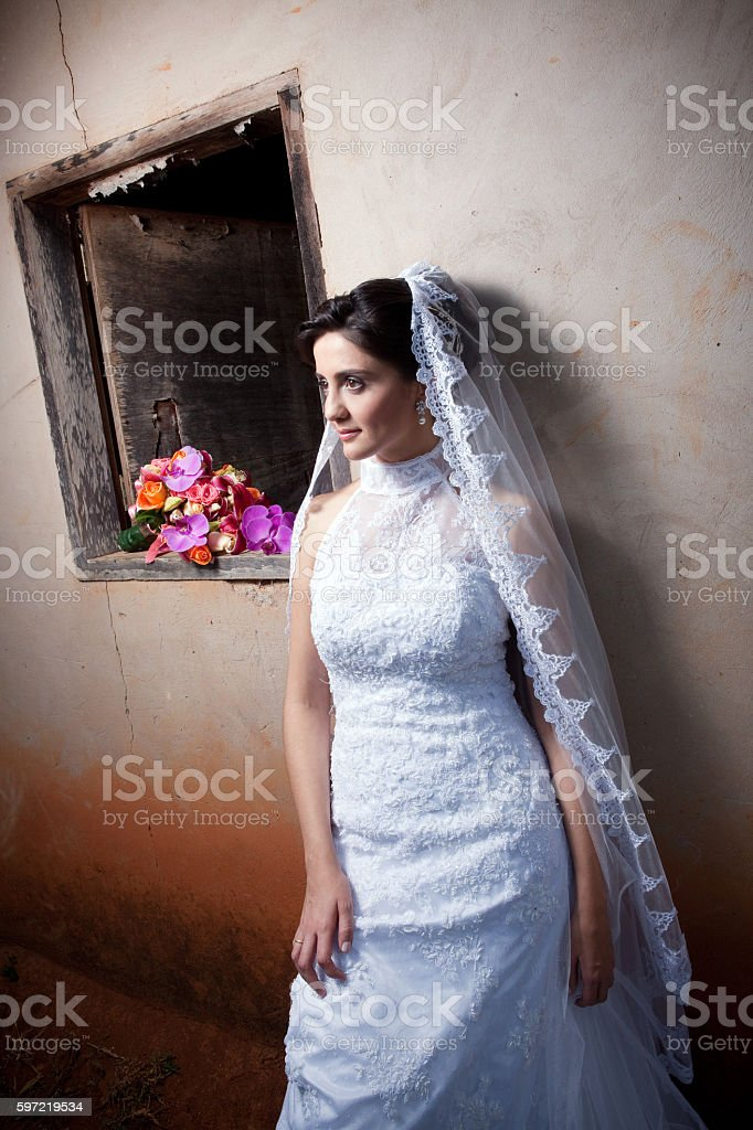 Young Bride Posing Outside Old Country House Window and Bouquet foto royalty-free