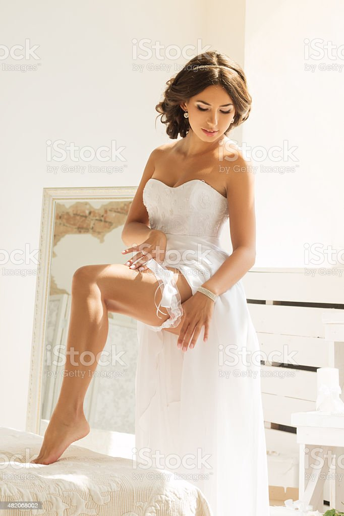 Young bride putting garter on her leg stock photo