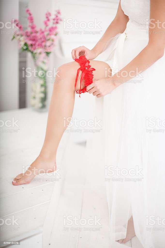 Young Bride Putting On Red Grater stock photo