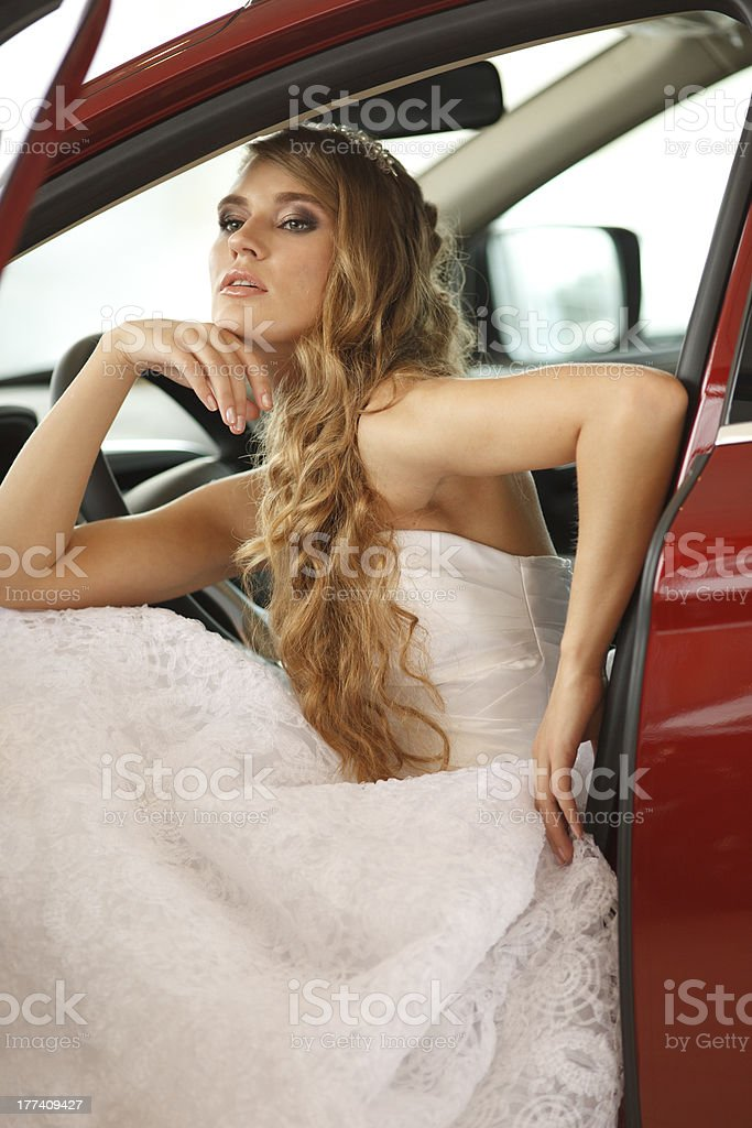 Young bride sits in car royalty-free stock photo
