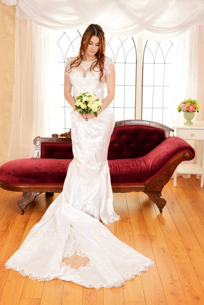 young bride with bouquet standing in front of large window - hochzeitskleider canda stock-fotos und bilder