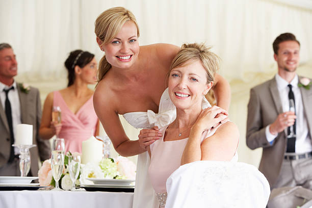 A young bride with her mother at a wedding reception stock photo