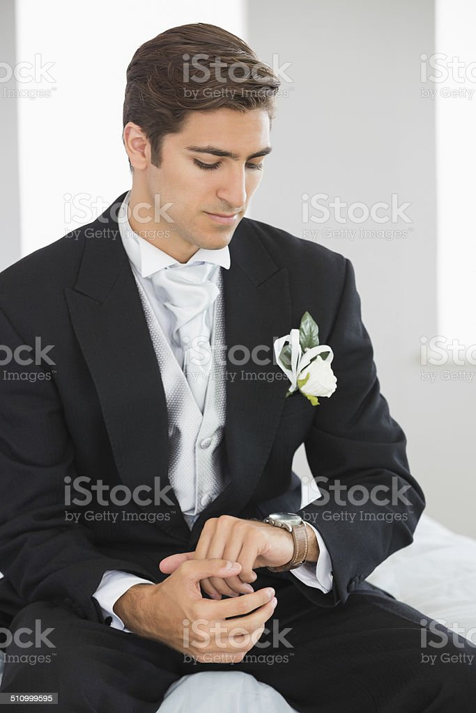Young bridegroom watching the clock stock photo