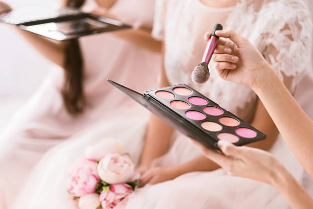 Young bridesmaid holding the palette of blusher Great palette of blusher. Pleasant good looking young bridesmaids sitting in the white bedroom while helping the bride to get ready and holding the palette of blusher blusher make up stock pictures, royalty-free photos & images