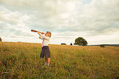 A young British girl dressed in business tie and skirt looks through a telescope at the top of a hill in Gloucestershire, United Kingdom. She is looking for new business opportunities.