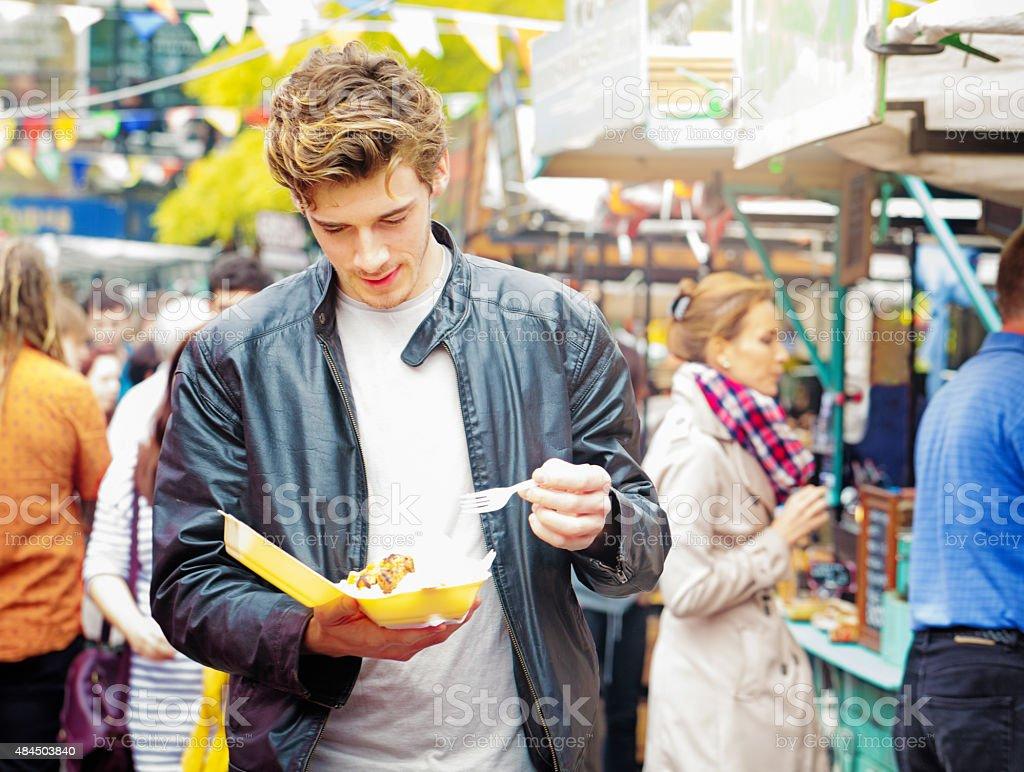 Young British man walking in market eating street food stock photo
