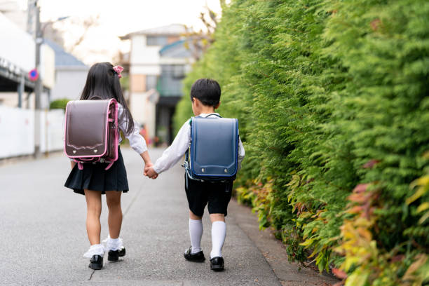 Young brother and sister walking to school together holding hands Young brother and sister walking to school together holding hands. Tokyo, Japan japanese school girl stock pictures, royalty-free photos & images