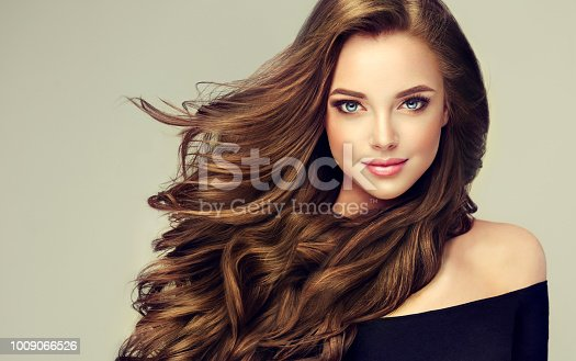 Young, brown haired woman  with voluminous hair.Beautiful model with long, dense, curly hairstyle and vivid makeup. Perfect dense, wavy,and shiny hair. Hairdressing art, hair care and beauty products.