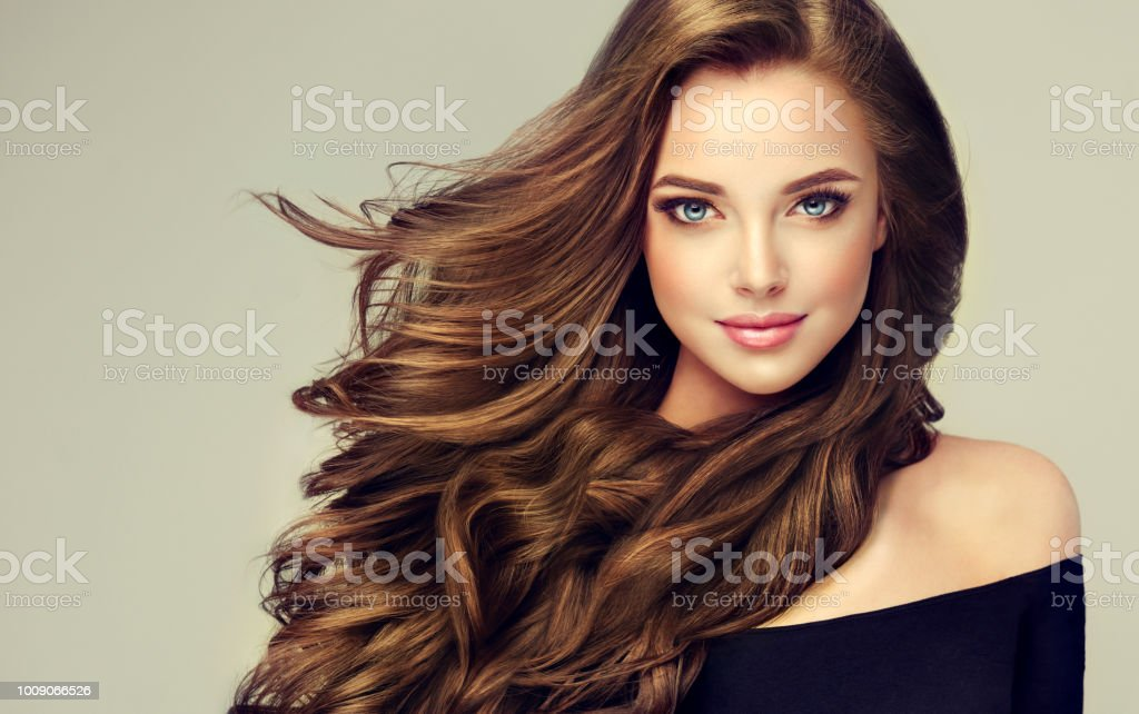 Junge, braunen Haaren schöne Modell mit langen, lockigen, gepflegtes Haar. Ausgezeichnete Haare Wellen. Friseur-Kunst und Haare Pflege. – Foto